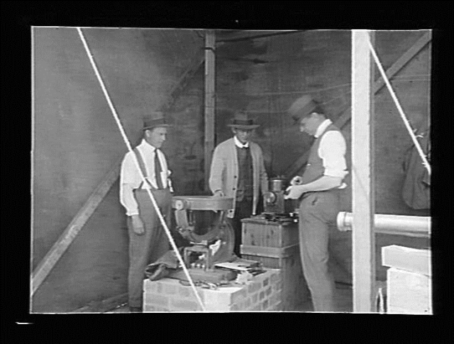 Three men using astronomical equipment