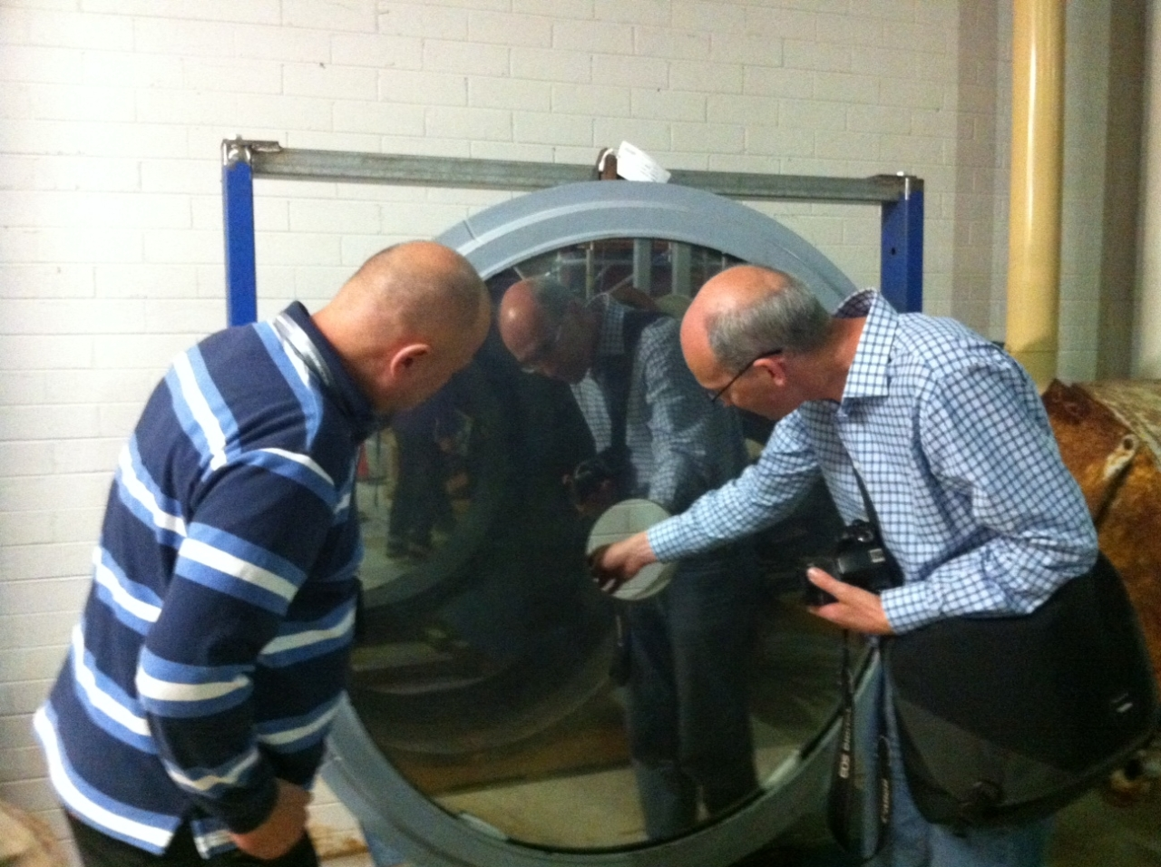 Two men inspect a large circular mirror